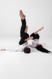 Młodzi i wdzięczni tancerze baletowi w minimalistycznym czarnym stylu na białym tle studyjnym