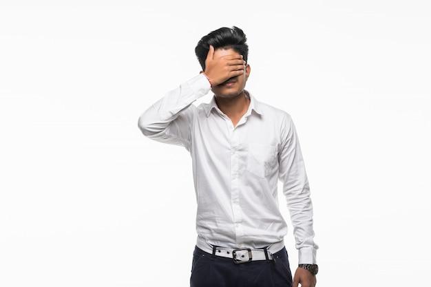 Młodzi indyjscy przystojni mężczyzna pokrywy oczy odizolowywający na biel ścianie