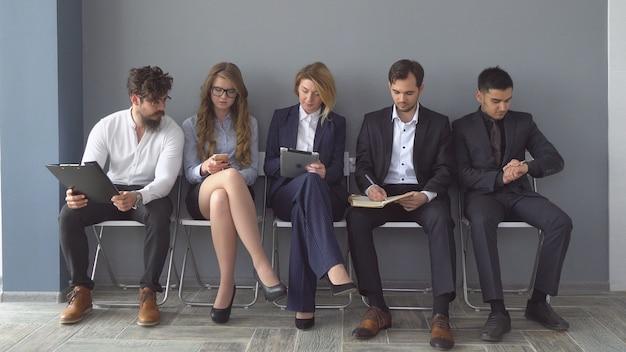 Młodzi kandydaci czekają na rozmowę kwalifikacyjną. grupa młodych ludzi nudziła się na rozmowę o pracę. rekrutacja do firmy.