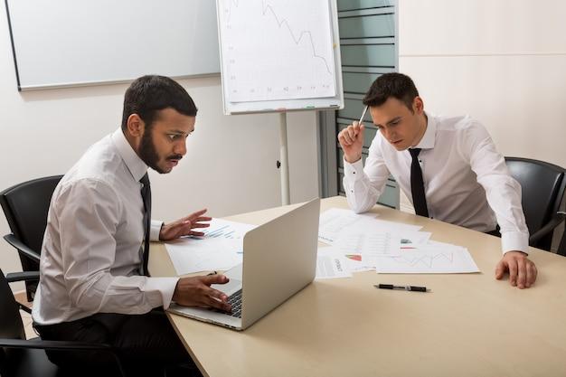 Młodzi karierowicze opracowują biznesplan kreatywni ludzie biznesu omawiają projekt biznes...