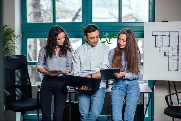 Młodzi kaukascy architekci lub projektanci używający palety kolorów do nowego projektu na laptopie w stylowym nowoczesnym biurze z dużym oknem.