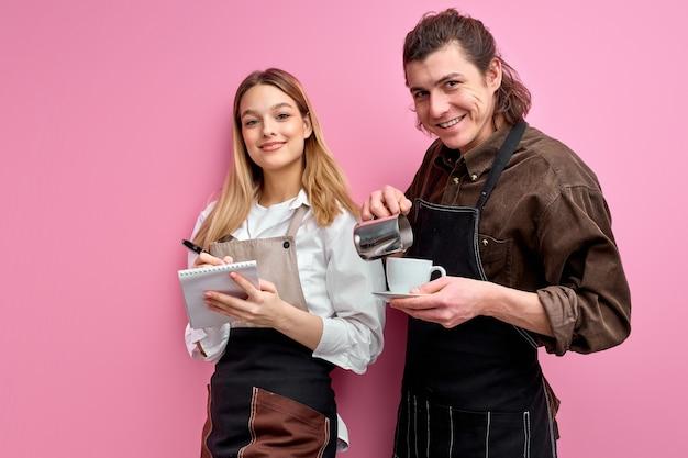 Młodzi kelnerzy gotowi służyć klientom w kawiarni lub restauracji, stoją na białym tle na różowym tle aparatu fotograficznego