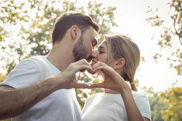 Młodzi kochankowie całują się, gotowi połączyć ręce, by uformować serce w parku. nastoletnie pary okazują sobie miłość w parku. koncepcja młoda para w parku.