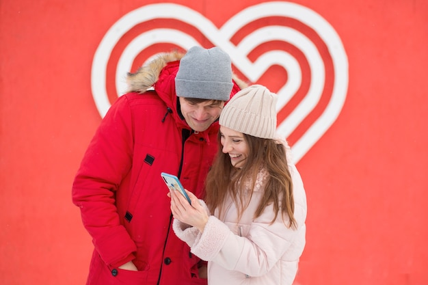 Młodzi kochankowie z telefonem w pobliżu wielkiego serca. walentynki