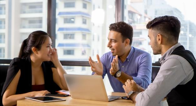 Młodzi koledzy biznesowi spotykający się i pracujący na komputerze, pracujący razem nad projektem.