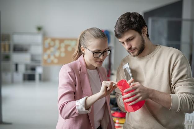 Młodzi koledzy omawiają czerwony obiekt geometryczny właśnie wydrukowany na drukarce 3d, podczas gdy bizneswoman coś wyjaśnia
