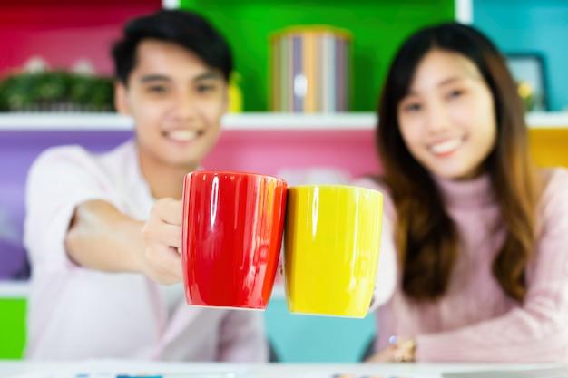 Młodzi koledzy pije napój podczas pracy