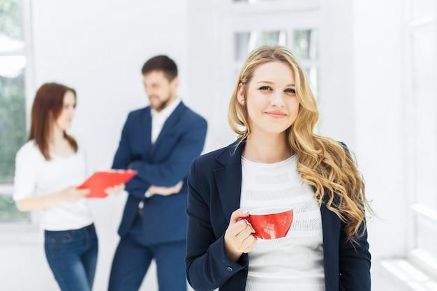 Młodzi koledzy po przerwie na kawę, rozmawiając w biurze