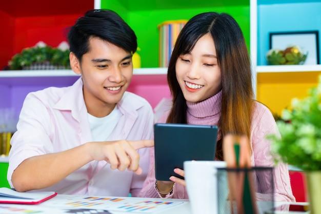 Młodzi koledzy pracujący razem w nowoczesnym biurze