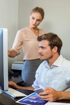 Młodzi koledzy pracuje na komputerze przy biurkiem