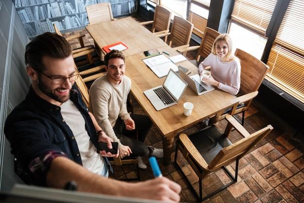 Młodzi koledzy siedzi podczas gdy praca z laptopami i biurkiem
