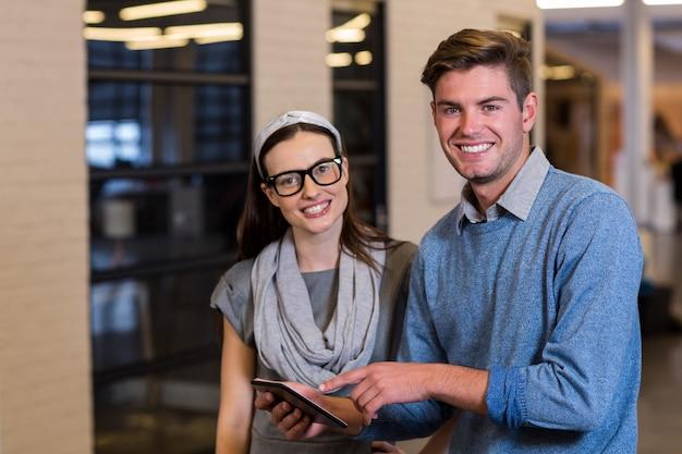 Młodzi koledzy używa cyfrową pastylkę w biurze