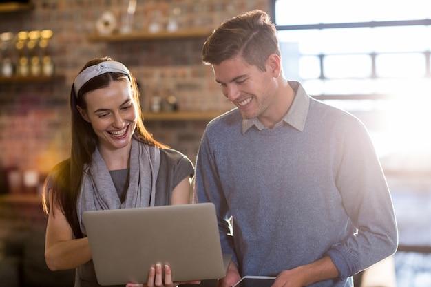 Młodzi koledzy używa laptop w biurze