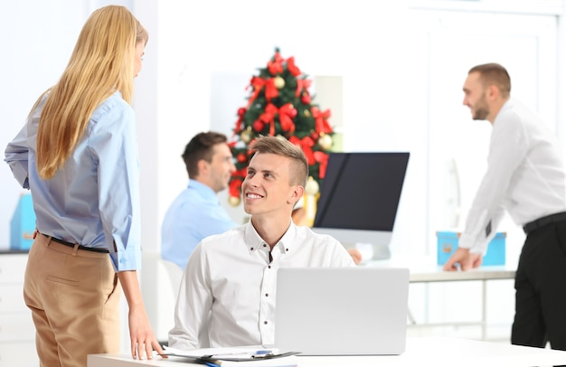 Młodzi koledzy w biurze udekorowani na boże narodzenie