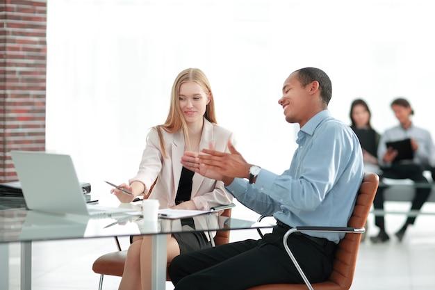 Młodzi koledzy z biznesu rozmawiają za biurkiem .photo z miejscem na tekst