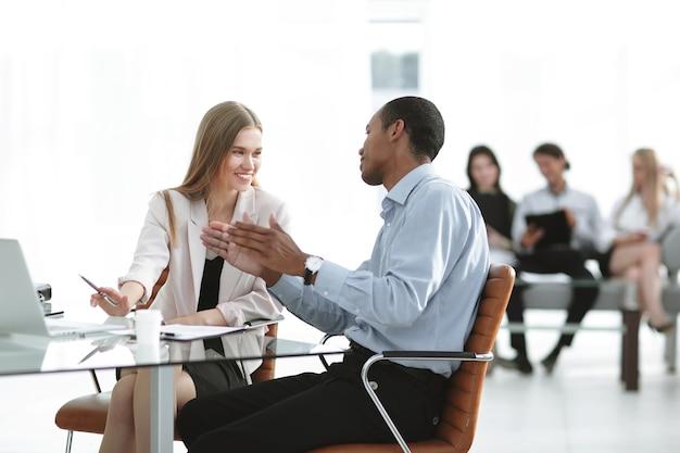 Młodzi koledzy z biznesu rozmawiają za biurkiem
