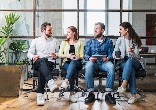 Młodzi koledzy z firmy siedzą w rzędzie i rozmawiają ze sobą