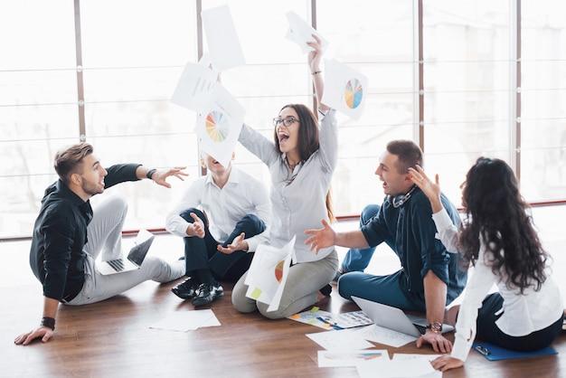 Młodzi kreatywni ludzie w nowoczesnym biurze. grupa młodych ludzi biznesu współpracuje z laptopem. freelancerzy siedzą na podłodze. współpraca korporacyjna. koncepcja pracy zespołowej