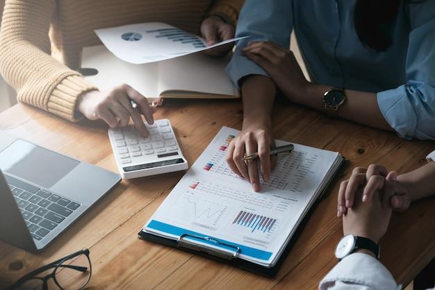 Młodzi księgowi konsultanci zespołu marketingu i korzystający z kalkulatora do analizy wzrostu sprzedaży na globalnym rynku pracy. koncepcja rachunkowości