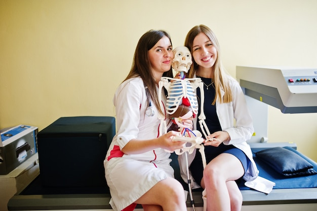 Młodzi lekarze bawią się, stwarzając ze szkieletem.