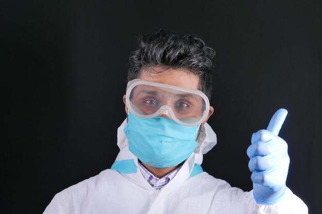 Młodzi lekarze wręczają rękawiczki medyczne pokazując kciuk