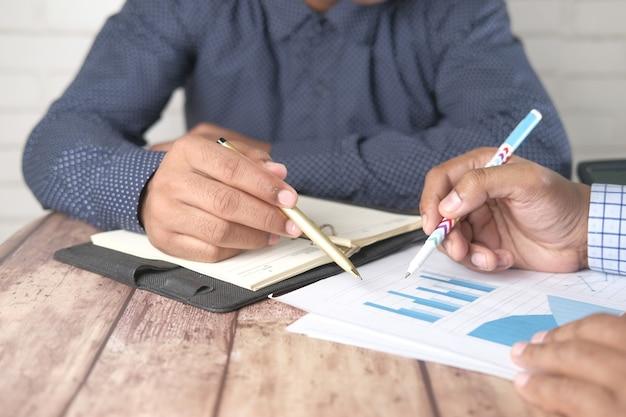 Młodzi ludzie analizując dane finansowe na biurku