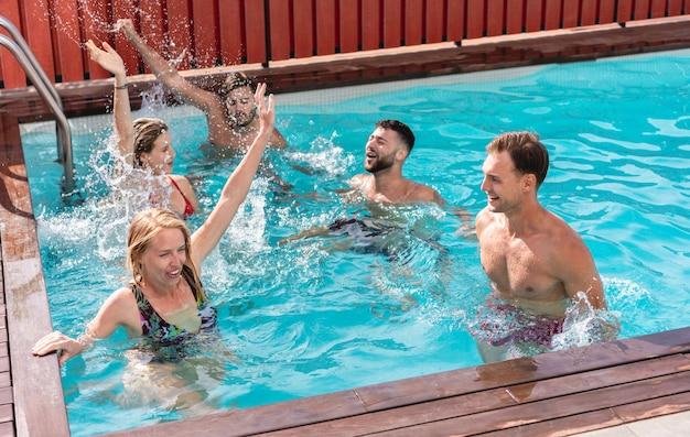 Młodzi ludzie bawią się na ekskluzywnej imprezie w willi w basenie