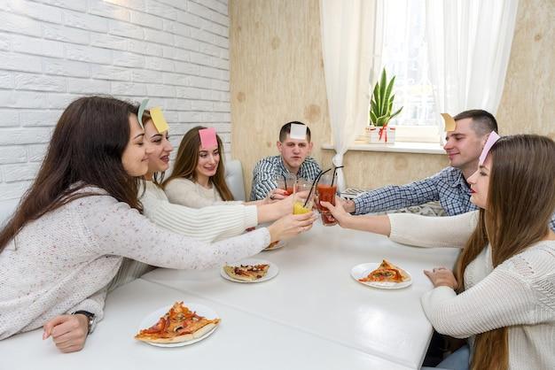 """Młodzi ludzie bawią się w """"zgadnij kto"""", jedząc pizzę w kawie"""
