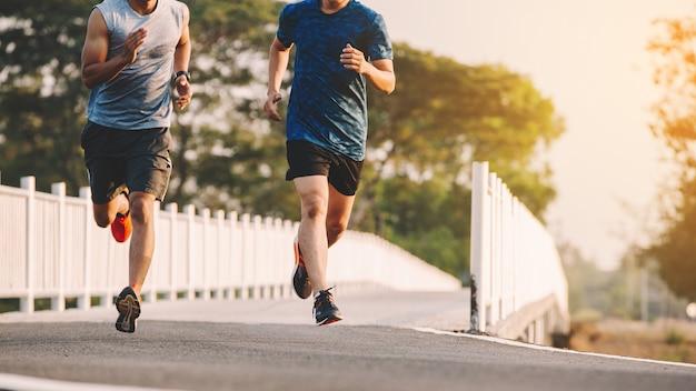 Młodzi ludzie biegacz działa na drodze do biegania w parku miejskim
