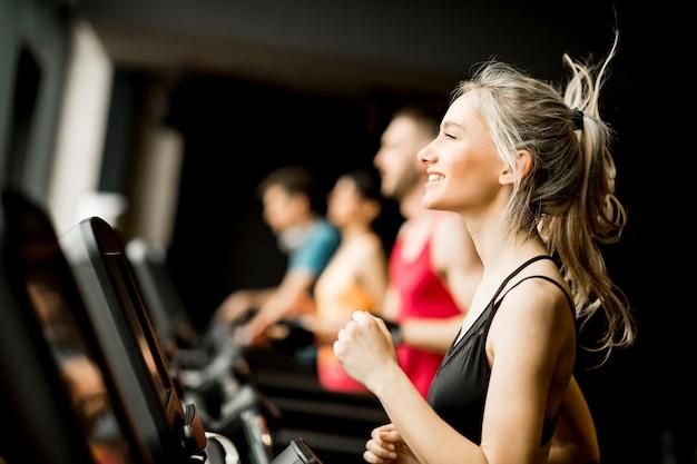 Młodzi ludzie biegają na bieżniach w nowoczesnej siłowni