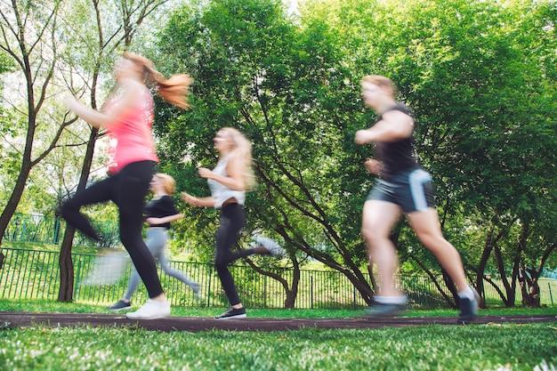 Młodzi ludzie biegający w parku. niewyraźne z szybkiego obrazu.