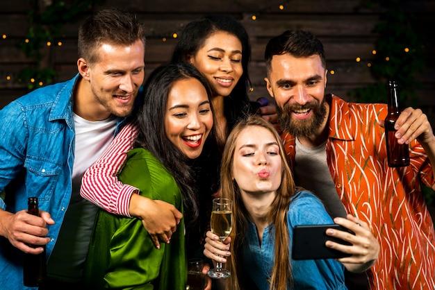 Młodzi ludzie biorący selfie razem