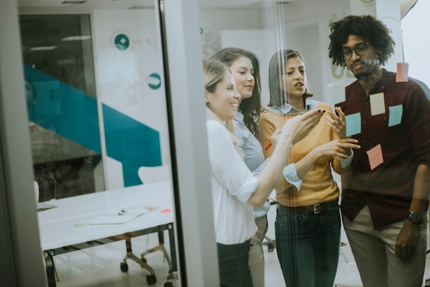 Młodzi ludzie biznesu dyskutuje przed szklaną ścianą używać poczta zauważa i majcherów