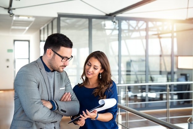 Młodzi ludzie biznesu omawiają i planują wyniki na korytarzu biurowym