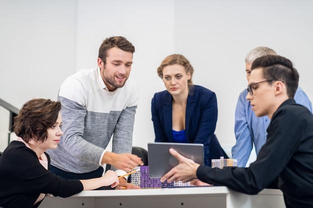 Młodzi ludzie biznesu omawiający nowy projekt w sali konferencyjnej.