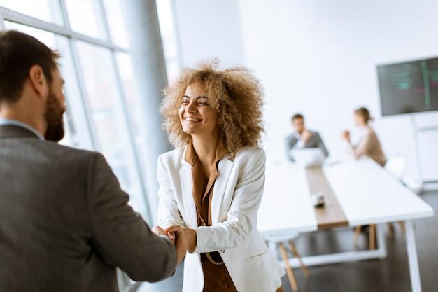 Młodzi ludzie biznesu podają sobie ręce w biurze