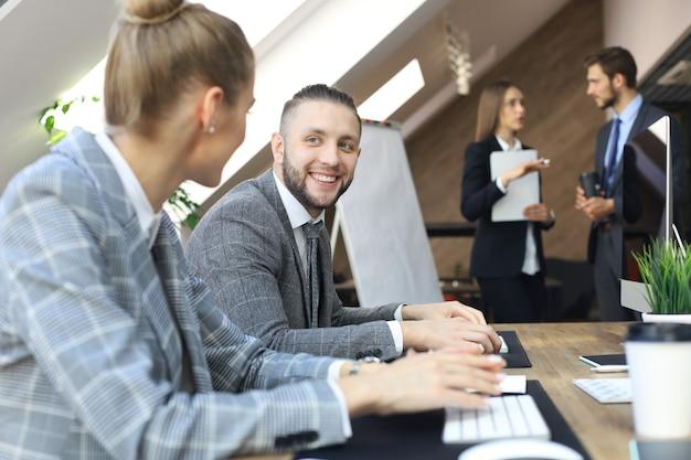Młodzi ludzie biznesu pracujący na komputerach stacjonarnych w nowoczesnej przestrzeni biurowej.