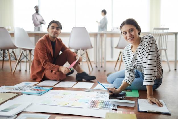 Młodzi ludzie biznesu siedzi na podłodze