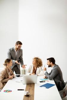 Młodzi ludzie biznesu siedzi przy stole spotkania w sali konferencyjnej, omawiając strategię pracy i planowania