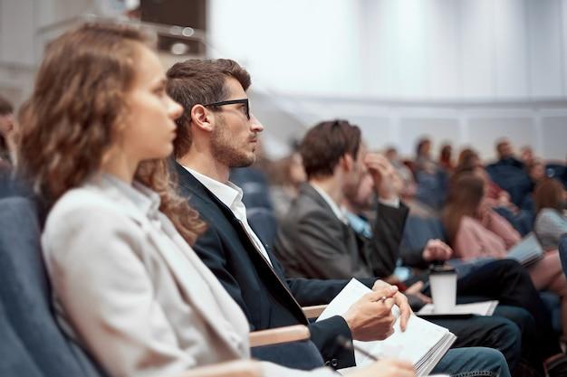 Młodzi ludzie biznesu słuchający wykładu w sali konferencyjnej