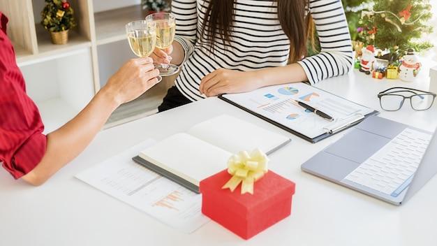 Młodzi ludzie biznesu świętują wakacje w nowoczesnym biurze w ostatni dzień roboczy.
