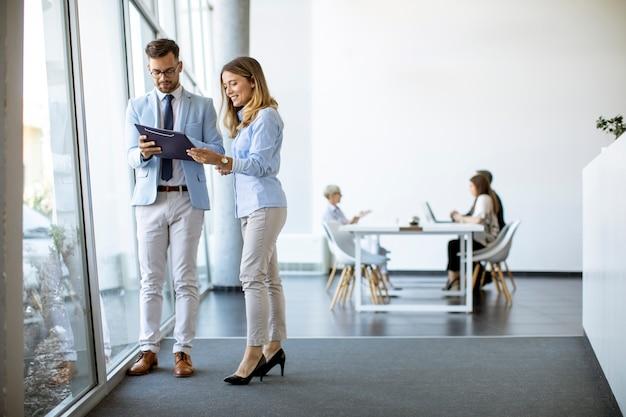 Młodzi ludzie biznesu szukają pliku w nowoczesnym biurze