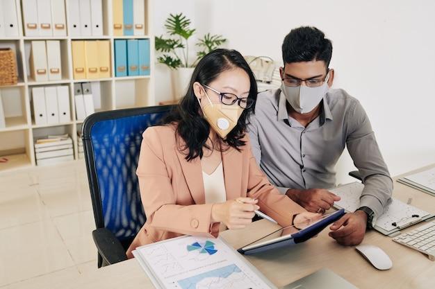 Młodzi ludzie biznesu w maskach ochronnych podczas omawiania raportów i planów rozwoju biznesu na spotkaniu