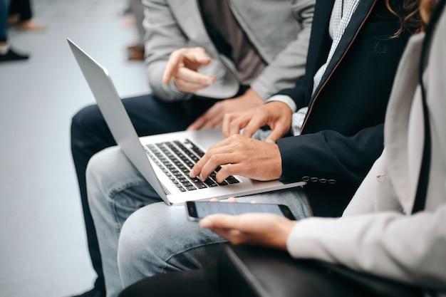 Młodzi ludzie biznesu za pomocą laptopa siedząc w wagonie metra