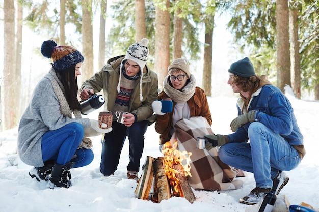 Młodzi ludzie, camping w zimowym lesie
