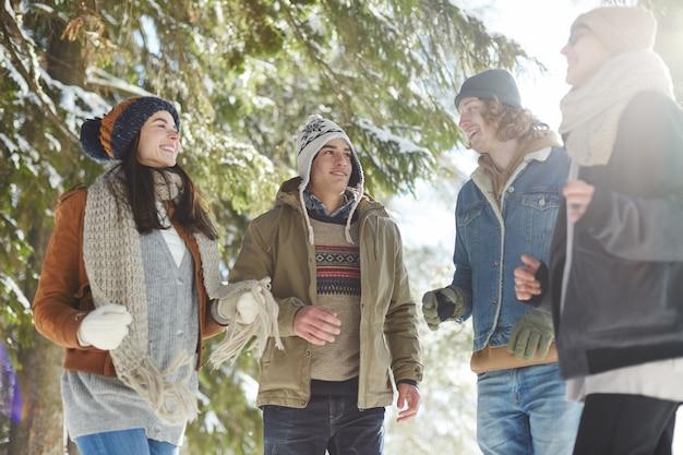 Młodzi ludzie chodzą w zimowym lesie