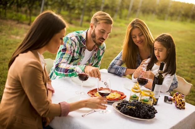 Młodzi ludzie delektują się kolacją i degustacją wina w winnicy
