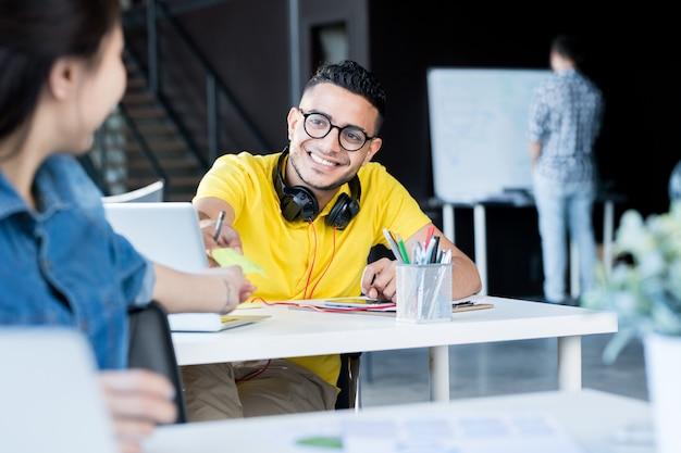 Młodzi ludzie dzielą się notatkami w biurze