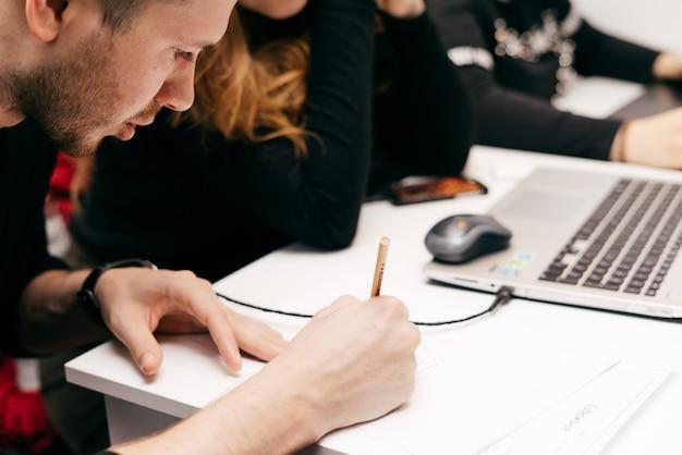 Młodzi ludzie, graficy pracujący razem nad projektem w biurze