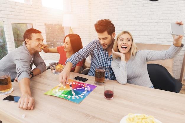 Młodzi ludzie grają w gry planszowe za pomocą kości i żetonów.